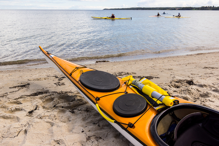A yellow kayak on the beach and four kayaking along the shore, Holl, Denmark, August 27, 2017 Editorial