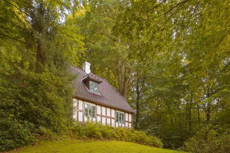 Old half-timberd white house on a hilltop in the green forest, Vejle, Denmark, August 25, 2017 Stock Photo