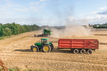Tractor and combine engaged in harvesting grain, Borkop, Denmark , August 27, 2017 Editorial