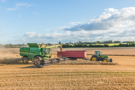 Harvesting in a yellow field by tractor and combine, Borkop, Denmark , August 27, 2017 Editorial