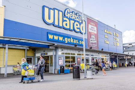 Walkingwith shopping carts to the entrance of GeKas in Ullared, September 3, 2017 Editorial