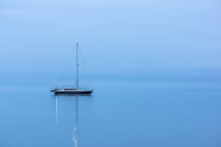 Lonely Black sailing boat in the ocean before sunrise, reflections in blue hour