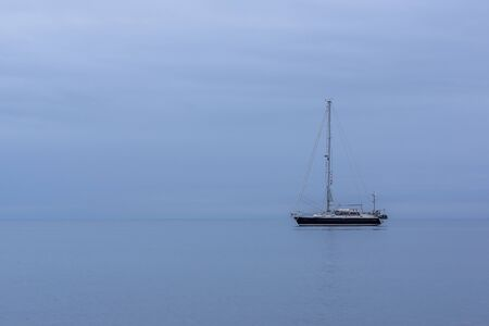 Black sailing boat alone in the ocean during blue hour Stock Photo