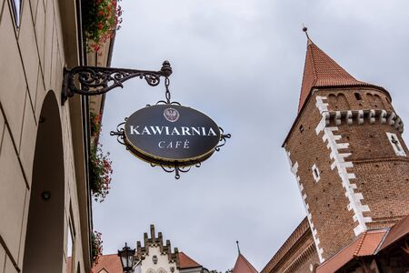 Cafe sign in old town and the tower of the city wall, Krakow, Poland September 17, 2017