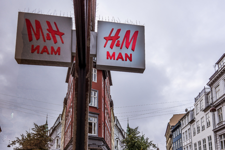 HM man sign reflections in a store window, against blue sky, Copenhagen, Denmark, September 21, 2017 Editorial