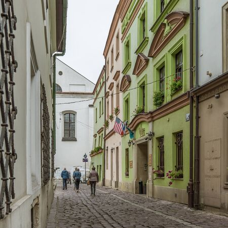 Narrow alley in the jewish district with a green hotel ant the american flag, Krakow, Poland, September 16, 2017