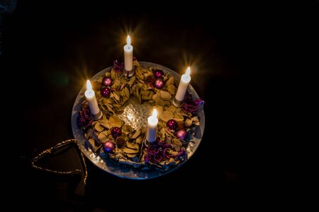 Advent wreath with four burning candles on a silver barrel, standing on  on a black table with glasses. Frederikssund, Denmark, Dec 30, 2016, Stock Photo