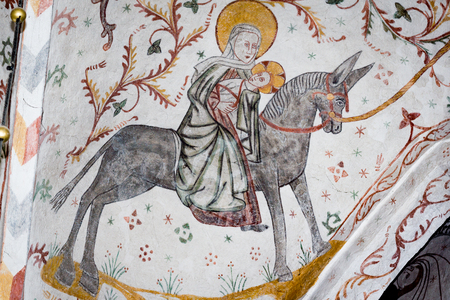 Medieval fresco of the flight into Egypt, Mary and the christ child on a donkey, Tingsted church, Denmark - April 11, 2017
