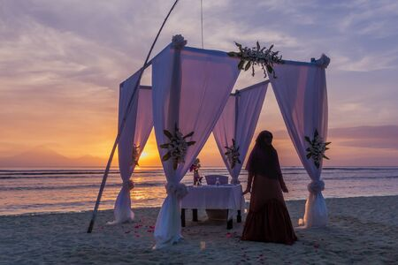 Muslim woman in a long brown dress standing in front of a luxory dinner table on the beach in the sunset, april 24, 2018, Gili Trawangan, Indonesia