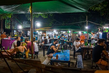 European turists and local residents sitting in the light of electrical bulbs at long tables having various streetfood in an indonesian nightmarket, april 23, 2018, Gili Trawangan, Indonesia