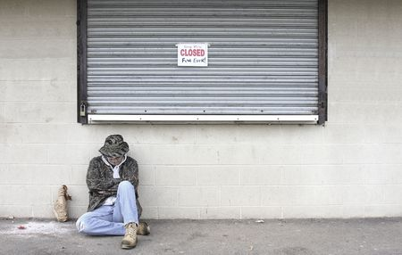 Homeless man sleeping on the street next to a business that has gone bankrupt