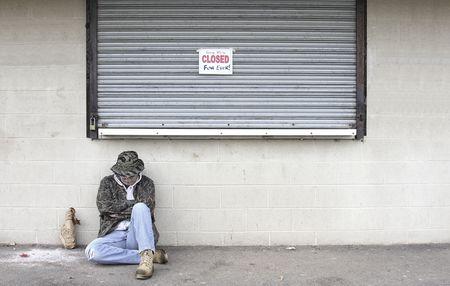 underprivileged: Senzatetto uomo dormire per strada accanto a un business che ha fallito