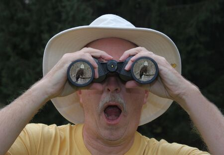 bird watcher: Man looking at Bald Eagle through binoculars Stock Photo
