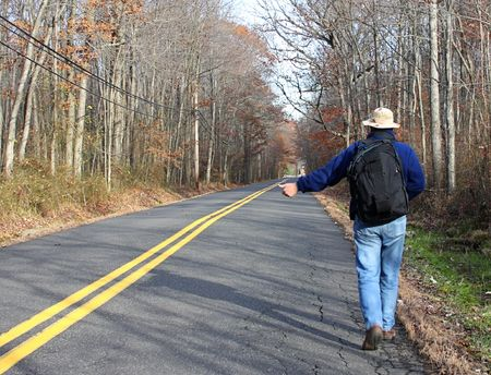 Man hitchhiking on a country road in fall Stock Photo