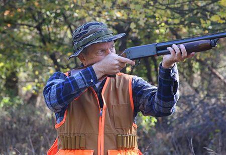 rifleman: Hunter shooting a shotgun in a field in fall Stock Photo