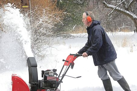 plows: Man Using A Snow Blower In Winter Stock Photo