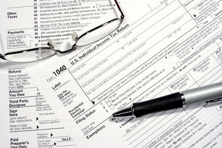 tax return: Close-up of a Federal Tax Return Form with glasses and a pen