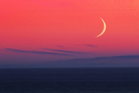 Crescent Moon Over the Pacific Ocean with a coloful sky