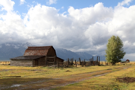 national parks: Iconic Mormon Row Barn which is a structure that is a part of Grand Tetons National Parks with the Teton Mountain Range in the background Stock Photo