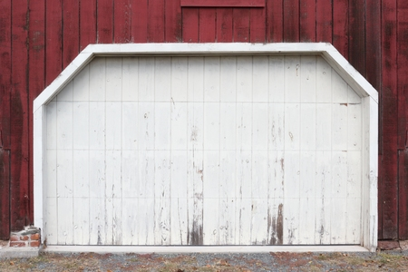building structures: Rustic old red and white barn door with peeling paint Stock Photo