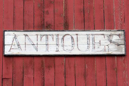 Antiques Sign on the side of an old red barn Stock Photo
