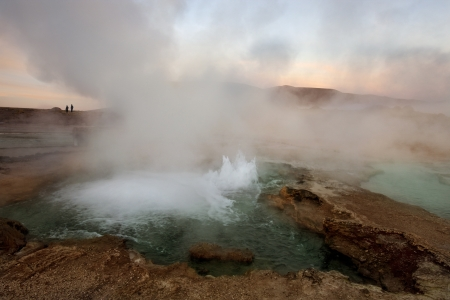 surmounted: El Tatio geyser field is located within the Andes Mountains of northern Chile at 4,200 meters above mean sea level  The best time to see them is at sunrise when each geyser is surmounted by a column of steam that condenses in the bitterly cold morning air