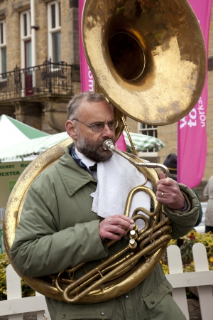 playing the market: A street musician playing the tuba at a market in the town of Malton in North Yorkshire in the United Kingdom.