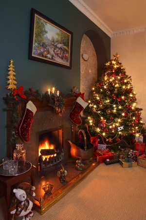 Celebrating Christmas in the home with a Christmas tree, gifts and a nice warm fire.