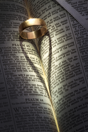 A wedding ring on an open bible casting a heart-shaped shadow  photo