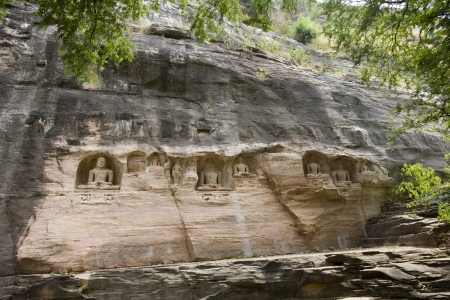 jainism: 7th century Jain sculptures depicting the Tirthankaras near Gwalior Fort in the of town of Gwalior in the Madaya Pradesh region of India  In Jainism, a Tīrthaṅkara is a human being who achieves moksa  enlightenment  Stock Photo