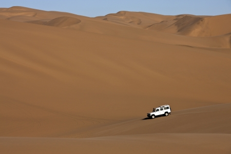 Four wheel drive vehicle in the sand dunes of the Namib-Naukluft Desert in Namibia photo