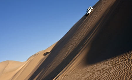 Driving in the sand dunes of the Namib Desert near Sandwich Bay on the coast of Namibia Standard-Bild