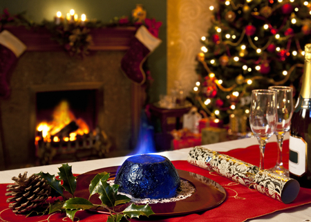 christmas cracker: A Christmas Pudding with burning brandy topping with a festive background of fireplace and Christmas tree