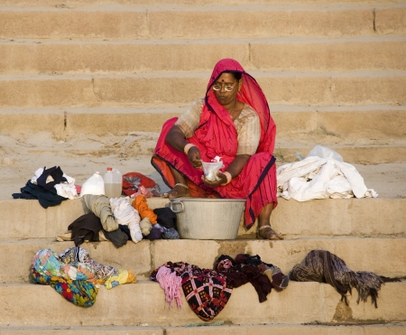 Indian woman washing clothes on the Hindu Ghats by the River Ganges in Varanasi in the Uttar Pradesh region of India.