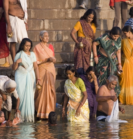 Group of pilgrims on the Hindu ghats on the banks of the Holy River Ganges (Ganga) in Varanasi (Benares) in the Uttar Pradesh region of northern India.