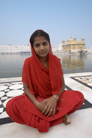 sikhism: Young Sikh girl at the Golden Temple of Amritsar in the Punjab region of northern India. The Golden Temple (Harmandir Sahib) is the holiest shrine in Sikhism.
