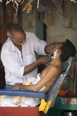 Barber at work on a street market in Srirangam in the Tamil Nadu region of southern India.