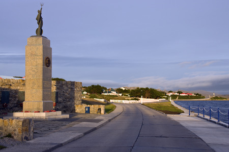 falklands war: The Falklands War Memorial with Government House in the background - Port Stanley in the Falkland Islands (Islas Malvinas).
