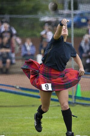 Sportswoman Putting the Shot at the Cowal Gathering. A traditional Highland Games held each year in Dunoon in Scotland Editorial