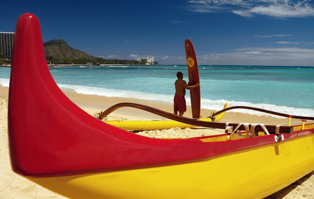 Outrigger canoe and surfer with a malabu surf board on Waikiki Beach near Diamond Head in Honolulu on the island of Oahu in Hawaii, USA.