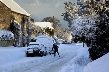 snow clearing: Clearing winter snow from vehicles in a small village in North Yorkshire in the United Kingdom