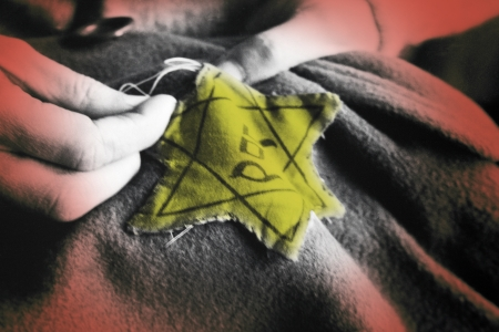 Old photograph of sewing on a Jewish Star - Auschwitz Concentration Camp, where up to three million people were murdered by the Nazis  2 5 million gassed, and 500,000 from disease and starvation