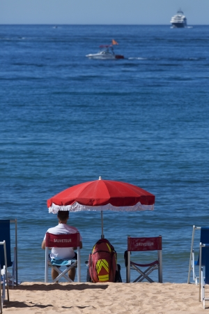 umbrela: A lifeguard on the beachfront at Cannes on the French Riviera in the South of France
