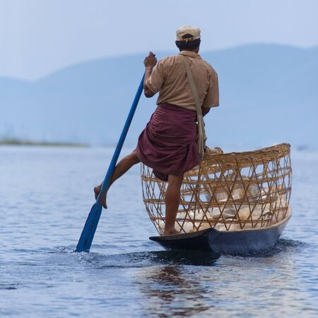A leg rowing fishermen on Inle Lake in Shan State in Myanmar - Burma - This unique style of rowing evolved because the shallow lake bottom is covered by reeds and plants making it difficult to see the fish while sitting - Standing gives a better view
