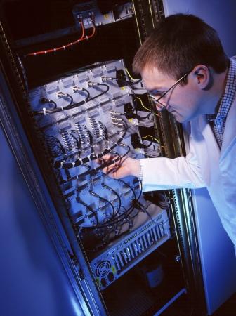 switchgear: An IT technician working on a mainframe computer