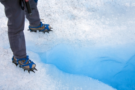 crampons: Standing over a crevasse on the Perito Moreno Glacier in the Andes Mountains of Patagonia in southern Argentina