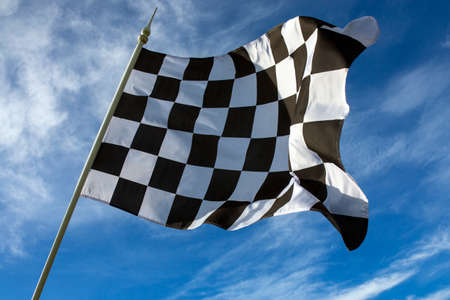Chequered Flag - Winner - The chequered flag is used to end a motor race  The flag is commonly associated with the winner of a race, as they are the first driver to  take   drive past  the chequered flag  Stock Photo