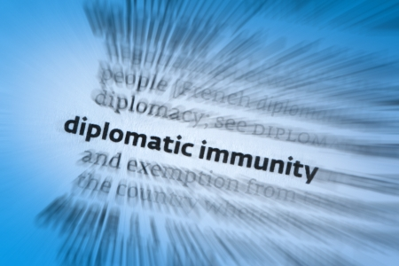 ensures: Diplomatic immunity is a form of legal immunity and a policy held between governments that ensures that diplomats are given safe passage and are considered not susceptible to lawsuit or prosecution under the host country Stock Photo