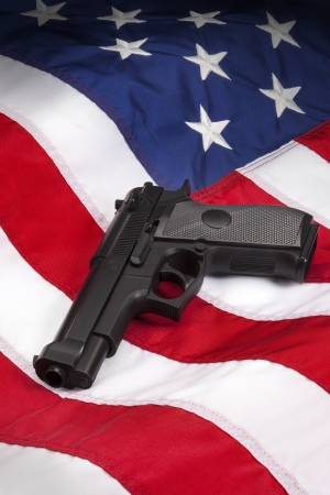 American Gun Law - Hand Gun on the flag of the United States of America  Stock Photo