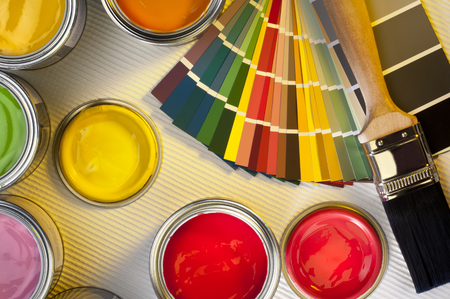 Selection of paint tester-pots with color charts and paintbrush  photo